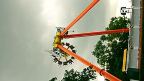 Scary giant metal wheel swing pendulum with people playing with excitement in an amusement park with dark cloudy sky thunder storm stock video footage