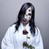 Scary girl. Go to sleep, white skin, dry rose Royalty Free Stock Photo