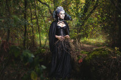 Scary girl witch in the forest. Scary girl witch in black clothes walking in the woods and collect dry grass royalty free stock photos