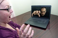 Scary hacker. A scary hacker coming through the screen of a laptop a young woman is using Royalty Free Stock Images