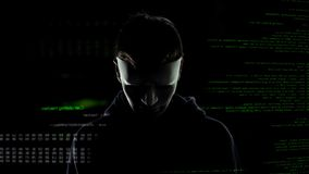 Scary hacker in white mask attacking personal data, codes and numbers background. Stock photo royalty free stock photo