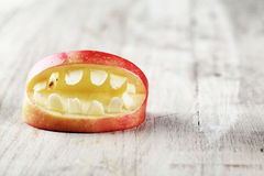 Scary Halloween apple mouth with teeth. Scary Halloween apple mouth with bared teeth on a textured white background with copyspace for your greeting or Stock Photo