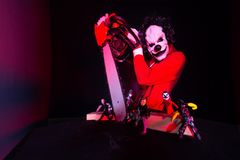 Scary halloween clown in red costume on black background. Killer clown holding a chainsaw.  royalty free stock photo