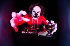 Scary halloween clown in red costume on black background royalty free stock image