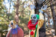 Scary Halloween clown toys chained to the tree. stock photography