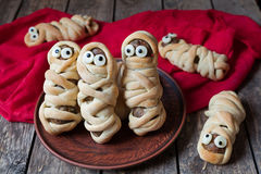 Scary halloween food meatball sausage mummies. Wrapped in dough with eyes  on vintage wooden background.  Halloween party decoration. Rustic style and natural Stock Images