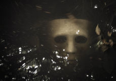 Scary Halloween mask drown in the water. White Scary Halloween mask drown in the water stock photography