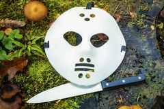 Scary Halloween mask and knife on stump Royalty Free Stock Photo