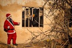 Scary Halloween monster versus Santa. Halloween monster threatening Santa Claus from inside a ruin Royalty Free Stock Photo