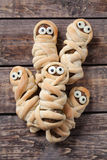 Scary halloween mummy sausages wrapped in dough Royalty Free Stock Image