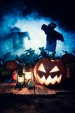 Scary Halloween pumpkin with blue mist and scarecrows. On dark background Royalty Free Stock Images