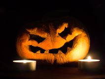 Scary Halloween pumpkin and burning candles on black background. Deep gaze royalty free stock image