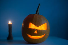 Scary Halloween pumpkin with eyes glowing inside at dark blue background stock images