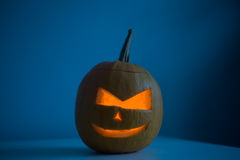 Scary Halloween pumpkin with eyes glowing inside at dark blue background Royalty Free Stock Images