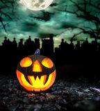Scary halloween pumpkin with graveyard Stock Photos