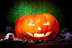 Scary Halloween pumpkin on a green wooden background Stock Photography