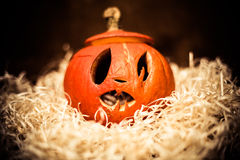 Scary Halloween pumpkin on hay Stock Image