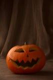 Scary halloween pumpkin jack-o-lantern. On dark background Stock Photos