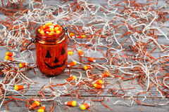 Scary Halloween pumpkin jar filled with candy. Horizontal image of scary pumpkin jar filled with Halloween candy surround by shredded paper and rustic wooden Royalty Free Stock Image