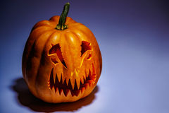Scary Halloween pumpkin with a shadow on a coloured background Stock Photo