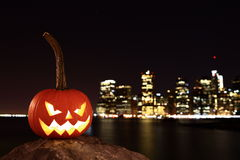 Scary Halloween's pumpkin. Scary pumpkin, symbol of Halloween, waiting for a celebrate on the shores of Brooklyn, against Manhattan Island, New York, United royalty free stock image