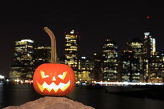 Scary Halloween's pumpkin. Scary pumpkin, symbol of Halloween, waiting for a celebrate on the shores of Brooklyn, against Manhattan Island, New York, United royalty free stock images