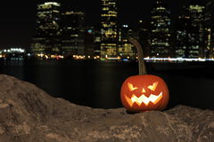 Scary Halloween's pumpkin. Scary pumpkin, symbol of Halloween, waiting for a celebrate on the shores of Brooklyn, against Manhattan Island, New York, United Stock Photo
