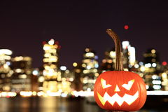 Scary Halloween's pumpkin. Scary pumpkin, symbol of Halloween, waiting for a celebrate on the shores of Brooklyn, against Manhattan Island, New York, United royalty free stock photo