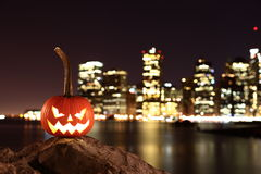 Scary Halloween's pumpkin. Scary pumpkin, symbol of Halloween, waiting for a celebrate on the shores of Brooklyn, against Manhattan Island, New York, United Royalty Free Stock Photos