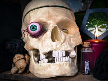 Scary Halloween Skull with eyeball. A witches shelf of ghoulish items including a skull, eyeball, potions, herbs and candle Royalty Free Stock Photos