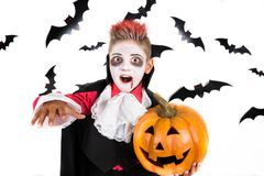 Scary Halloween vampire boy dressed up for spooky halloween party and holding an orange halloween pumpkin jack o lantern. Portrait of a Scary Halloween vampire stock photo