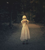 Scary Haunted Ghost Girl in Woods. A scary evil ghost girl wearing a white dress and face is walking in the dark woods with her hands up. Use it for a haunted Royalty Free Stock Image