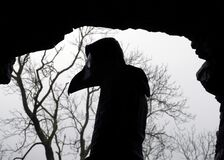 A scary hooded figure wearing a Halloween plague doctors mask. Standing in a cave