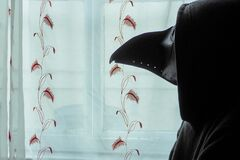 A scary, hooded figure wearing a plague doctor mask, looking out of a window