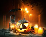 Scary horror background with halloween pumpkin jack o lantern. Placed on wooden deck. Old town street on background with glowing lamps. Halloween spooky royalty free stock photo