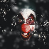 Scary horror circus clown laughing with evil smile. Closeup portrait on a scary horror circus clown laughing with evil smile among birthday party bubbles. Crazy