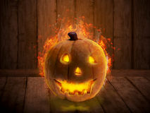 Scary Jack O Lantern with candle inside on the wooden floor Royalty Free Stock Photography