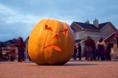 Scary Jack O'Lantern. Halloween pumpkin. Halloween celebrating. Behind pumpkin crowd of people Stock Image