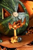 Scary Jack O Lantern halloween pumpkin. On dry leaves Stock Photo