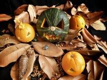 Scary Jack O Lantern halloween pumpkin. On dry leaves Stock Photography