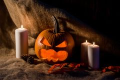 Scary jack-o-lantern, red leaves and candles. Close up image of carved pumpkin with scary face with red fallen leaves around and several burning candles Stock Images