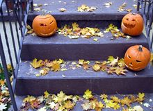Scary Jack O Lanterns. Three carved pumpkins wait on the steps to scare the children on Halloween stock images