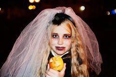 Scary kid as a zombie bride for trick or treat. With apple Stock Image