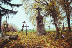 Scary leaning cross tomb stones in a foggy autumn scene in fall. Old creepy graves on cemetery in Slovakia. Spooky aged tombstones Stock Photo