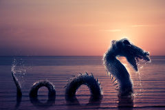 Scary Loch Ness Monster emerging from water. Photo composite of Loch Ness Monster Royalty Free Stock Photography
