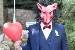 Scary looking elegant man holding a heart balloon