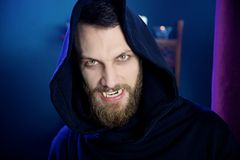 Scary male vampire looking camera with fangs. Horror vampire angry hungry showing fangs Stock Photo