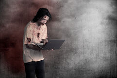 Scary male zombie typing with laptop. Over grunge background Royalty Free Stock Images