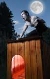 Scary man. Sitting on a doghouse and turning into werewolf Stock Image