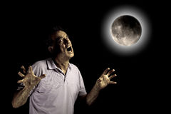 Scary Man Beast under Moon at Halloween. Scary Man Turning into Werewolf or Beast Under a Glowing Full Moon perhaps at Halloween Stock Photos